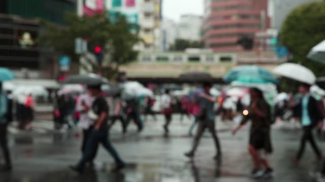 menge kreuzung stadt straße bei regen in den tag, mit unscharfen fokus - besichtigung stock-videos und b-roll-filmmaterial