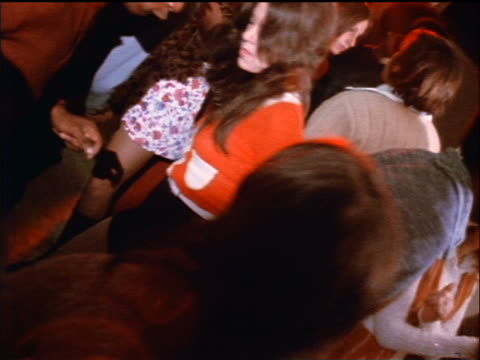 1974 canted crowd dancing at party indoors / documentary - 1974 bildbanksvideor och videomaterial från bakom kulisserna