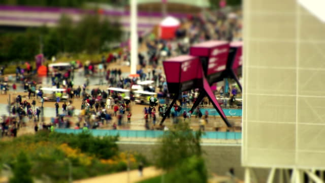 Crowd enter and exit in the rain over the main walk way at the London 2012 Paralympic ParkThere is TiltShift on this clip Timelapse Paralympic Park...