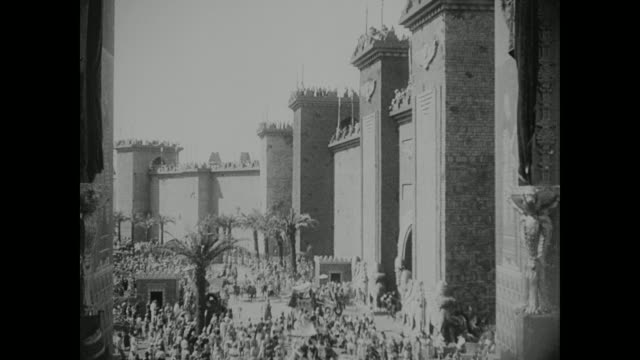 A crowd enters and exits through the gates to Babylon