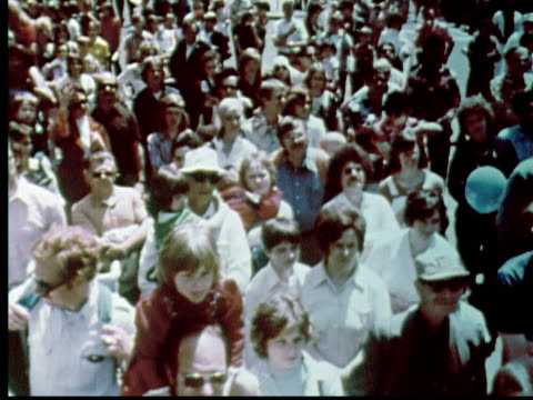 vídeos de stock e filmes b-roll de crowd facing camera on downtown philadelphia street. balloons in air. city hall in background . zoom into queen elizabeth of england, king of sweden,... - 1976