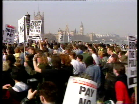 Crowd flowing away from camera over Lambeth Bridge with anti Poll Tax signs Houses of Parliament in distance 1990 Poll Tax demonstrations 31 Mar 90
