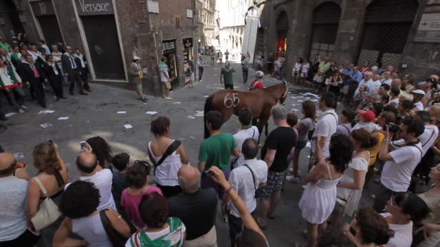 ws ha pan crowd following winning horse of palio down street / siena, italy - siena italy stock videos and b-roll footage