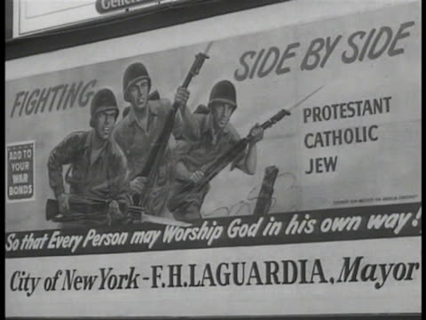 Crowd gathered around 'Fighting Side by Side Protestant Catholic Jew' billboard w/ New York Mayor Fiorello H LaGuardia religious leaders soldiers on...