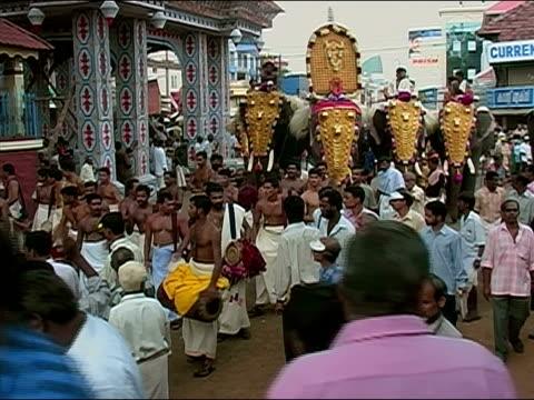 vidéos et rushes de crowd gathered around men playing drums / men riding elephants through streets during thrissur pooram elephant festival / thrissur, kerala, india - animaux au travail