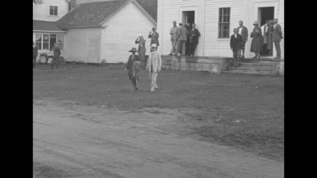a crowd gathered around the coolidge home / pres calvin coolidge and first lady grace coolidge walking to a large white clapboard church and entering... - coolidge calvin stock videos & royalty-free footage