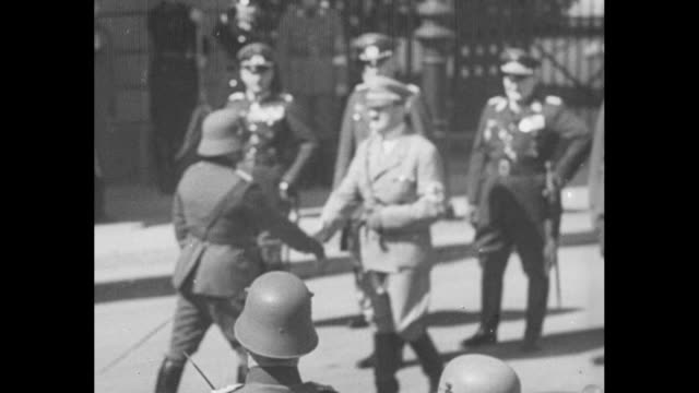 crowd gathered in street / adolf hitler with army officers walking along street in front of military band / hitler walks up to officer and shakes... - adolf hitler stock-videos und b-roll-filmmaterial