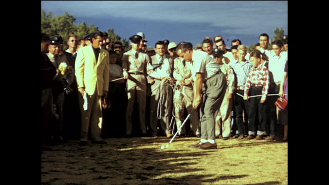 crowd gathered to watch bob hope play golf; people held back by white rope; people chasing the ball after the swing - ボブ ホープ点の映像素材/bロール