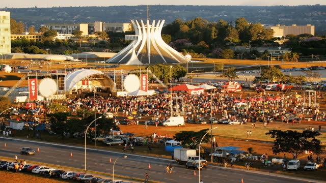 t/l, ha, ws, crowd gathering in front of outdoor concert stage  at metropolitan cathedral, brasilia, brazil - 前にいる点の映像素材/bロール