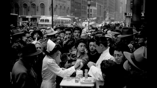 crowd gathers as a doctor and nurse give out vaccinations on a manhattan street doctor and nurse give out vaccinations on january 01 1949 in new york... - ワクチン接種点の映像素材/bロール