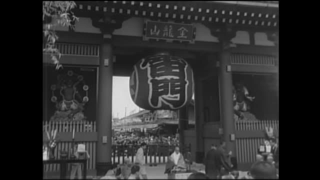 vídeos de stock, filmes e b-roll de a crowd gathers for the dedication ceremony of kaminarimon. - templo asakusa kannon