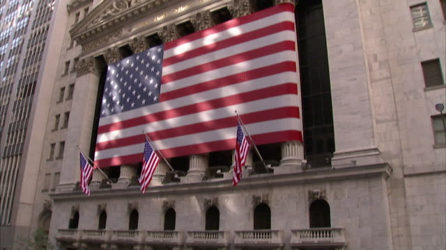 a crowd gathers on wall street across from a large american flag on the new york stock exchange. - ペディメント点の映像素材/bロール