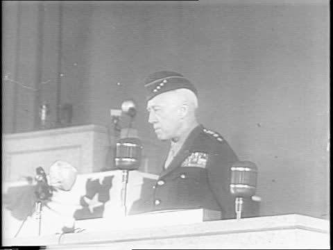 crowd / general george patton at speaker stand wearing overseas cap with four stars / patton speaks about seeing destroyed lands in germany and... - 1945点の映像素材/bロール