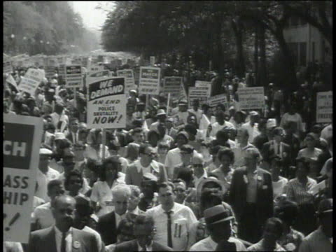 vídeos de stock e filmes b-roll de crowd holding signs marching / marchers waving flags and banners - 1963
