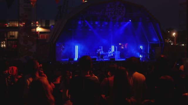 crowd illuminated as stage lights brighten, music festival crowd - popmusik konzert stock-videos und b-roll-filmmaterial
