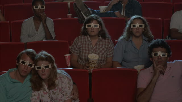 vídeos de stock, filmes e b-roll de a crowd in a movie theater starts clapping as fish are thrown at them. - óculos de terceira dimensão
