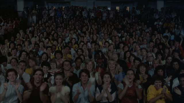 vídeos de stock, filmes e b-roll de a crowd in a movie theater starts clapping as the lights come up. - cinema