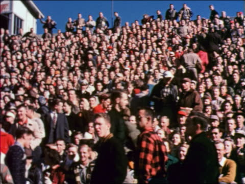 vídeos de stock e filmes b-roll de crowd in bleachers cheering at iowa state university football game / educational - 1951