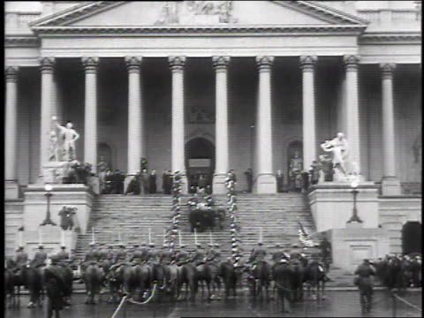 crowd in front of capitol as soldiers carry casket / soldiers carrying casket upstairs past honor guard / crowd of people with umbrellas entering... - 1930 stock-videos und b-roll-filmmaterial