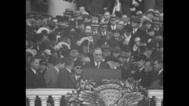 vídeos de stock, filmes e b-roll de up crowd in front of inaugural stand in front of us capitol bldg in background / ms franklin d roosevelt is sworn in by chief justice charles evans... - tomada de posse