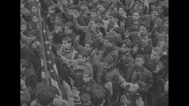 crowd in plaza of brooklyn borough hall / tiltdown crowd of white and black boy scouts raises arms in salute / vs scouts hold us flags chant sing /... - ボーイスカウト連盟点の映像素材/bロール