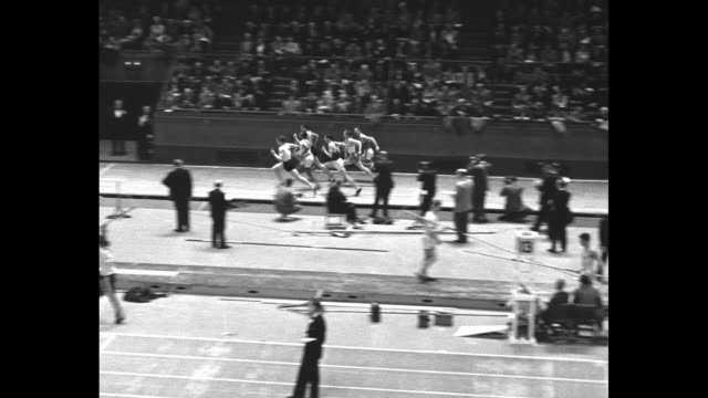 Crowd in stands at Madison Square Garden track and field meet / black runners and white runners take their marks / WS racers take off in backfield as...