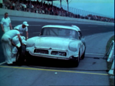 Crowd in stands some sitting on racetrack for first qualifiers of Daytona 500 Daytona International Speedway / pit crew hopping to work on 1962...