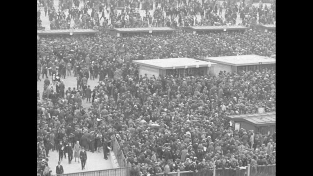 A crowd in the infield with the Eiffel Tower in the far distance and hundreds of people milling about / Wide shot of the grandstands at the Auteuil...