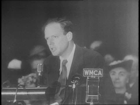 crowd in theater cheers with flags / shot of lindbergh surrounded by cameras / crowd claps / lindbergh passionately speaking to a rally in front of... - 1941年点の映像素材/bロール