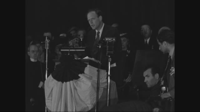 crowd in theater cheers with flags / shot of lindbergh surrounded by cameras / crowd claps / lindbergh passionately speaking to a rally in front of... - charles lindbergh stock videos & royalty-free footage
