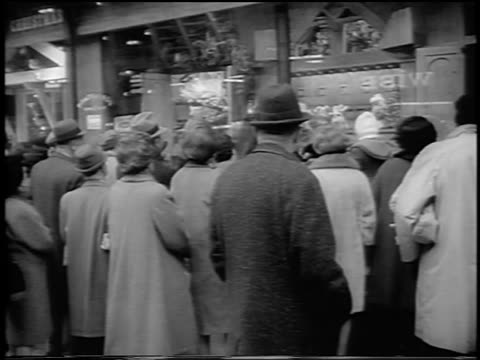 stockvideo's en b-roll-footage met b/w 1963 rear view crowd in winter coats looking at christmas display window of store / nyc - etalage