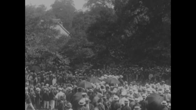 crowd is gathered outside somewhere in tokyo / man stands on platform and speaks to crowd, protesting the us's asian exclusion act of 1924 / crowd... - 税関点の映像素材/bロール