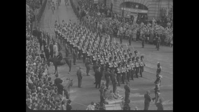 crowd lined streets procession military band soldiers royal coach with footmen cu people in the crowd queen juliana waving from coach - フットマン点の映像素材/bロール