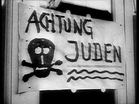 Crowd looking on as Nazi paints Star of David on Jewish shop window / Achtung Juden sign with skull and cross bones / Nazi Brownshirts looking at...