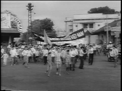 b/w 1963 crowd marching with banners on street at celebration rally / south vietnam / newsreel - south vietnam stock videos & royalty-free footage