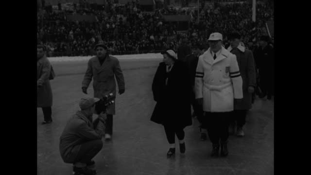 crowd milling about in front of bislett stadium ice rink prior to opening ceremony of 1952 winter olympics / two shots of people inside ice rink /... - cerimonia d'apertura video stock e b–roll