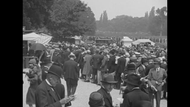 crowd milling about on grounds of longchamp racecourse / man at betting window buying ticket / crowd on grounds milling about pan across crowd / two... - 1920 stock videos & royalty-free footage