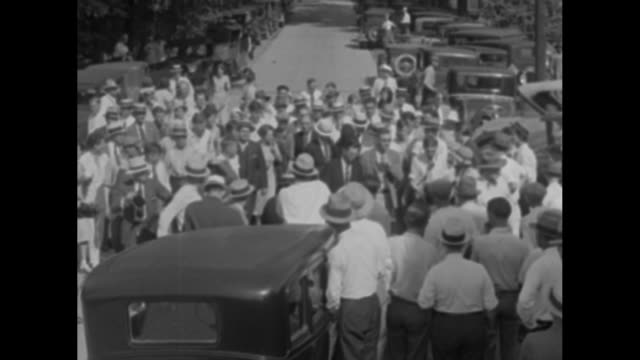 Crowd milling about on street in Wentworth / two shots of actress Libby Holman Reynolds walking through crowd towards courthouse wearing black veil...