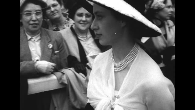 stockvideo's en b-roll-footage met crowd mills about on grounds beside ascot racecourse / queen elizabeth ii and uncle prince henry walk through crowd followed by princess margaret /... - prinses margaret windsor gravin van snowdon