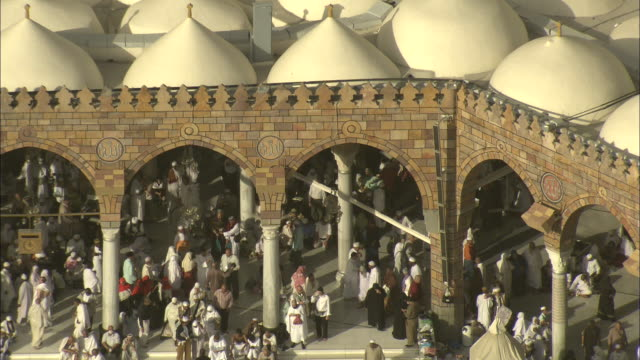 A crowd mills around an arched mosque in Mecca.