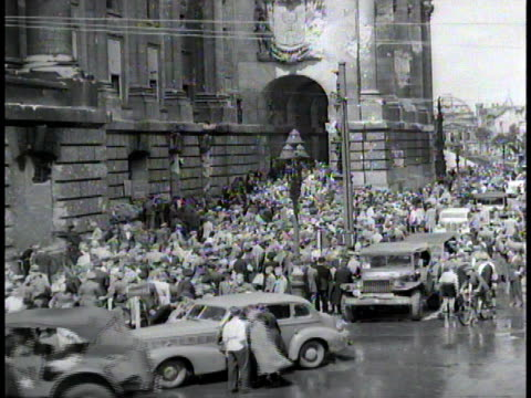 vidéos et rushes de crowd mingling in front of reichstag building with cars parked along curb / berlin germany - plan grue