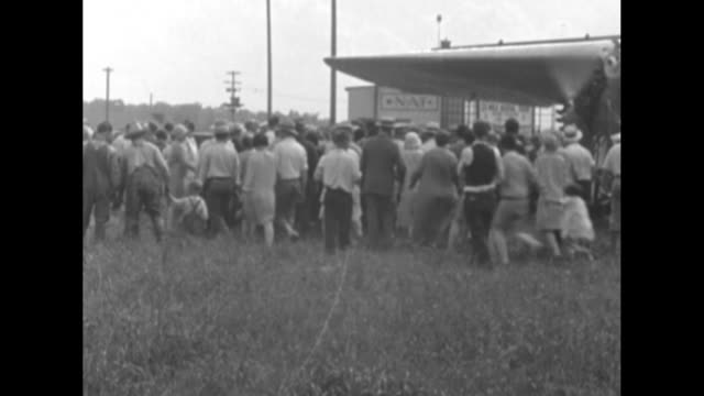 crowd moves away from small airplane as its propellers whirl and it prepares to depart / amelia earhart waves from passenger seat of plane / plane... - abheben aktivität stock-videos und b-roll-filmmaterial