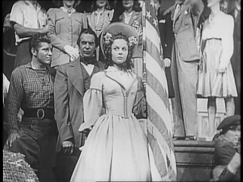 crowd of actors in period costume including susan hayward and robert preston massed around cecil b demille as he reads into a cbs microphone /... - amerikanischer treueschwur stock-videos und b-roll-filmmaterial