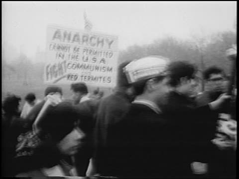 b/w 1967 crowd of antipeace demonstrators with anticommunist signs / central park nyc / newsreel - anti comunista video stock e b–roll