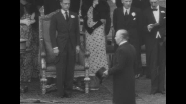 Crowd of attendees and debutantes at King Edward VIII's first garden party at Buckingham Palace in London / King stands in front of chair nods in...