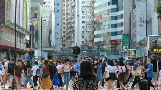 crowd of busy commuters with protective face mask crossing street in downtown district during rush hour, with highrise city buildings and busy traffic in background - office block exterior stock videos & royalty-free footage