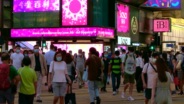 crowd of busy commuters with protective face mask crossing street in busy downtown district during rush hour at dusk, against city buildings with illuminated and colourful billboards and commercial signs - zebra crossing stock videos & royalty-free footage