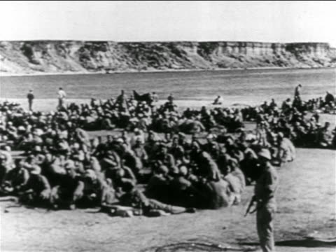 crowd of captured egyptian soldiers sitting on ground by suez canal / suez crisis - 1956 stock-videos und b-roll-filmmaterial