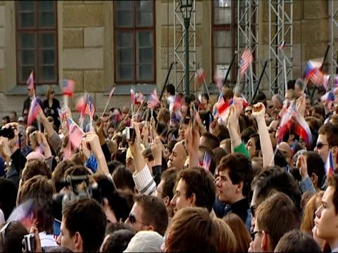 crowd of cheering people waving us and czech flags ahead of obama's address on 5 april 2009 / prague czech republic - アナモルフィック点の映像素材/bロール
