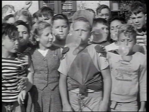 b/w 1947 crowd of children blowing bubbles with gum outdoors / newsreel - bubble gum stock videos & royalty-free footage